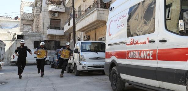 Membros dos capacetes brancos, grupo de socorristas civis da Síria, partem para um resgate após aviso de bombardeio  - AFP
