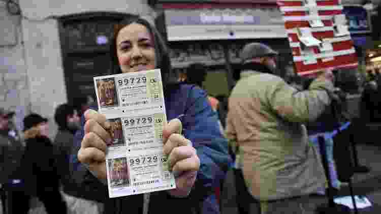 """Jovem segura bilhetes do grande sorteio de natal da Espanha, conhecido como """"El Gordo"""" - Dani Pozo/AFP"""