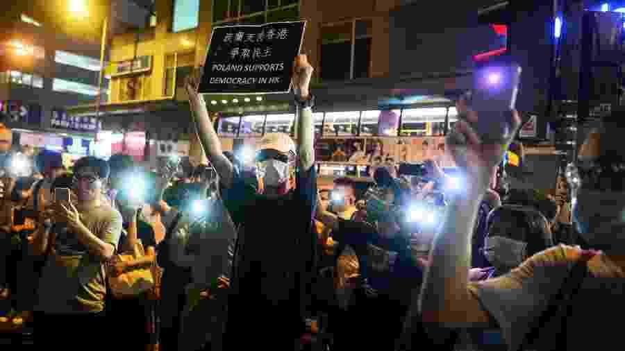 7.set.2019 - Manifestantes usam a lanterna do celular para protestar do lado de fora de uma delegacia de polícia em Hong Kong - Philip Fong/AFP