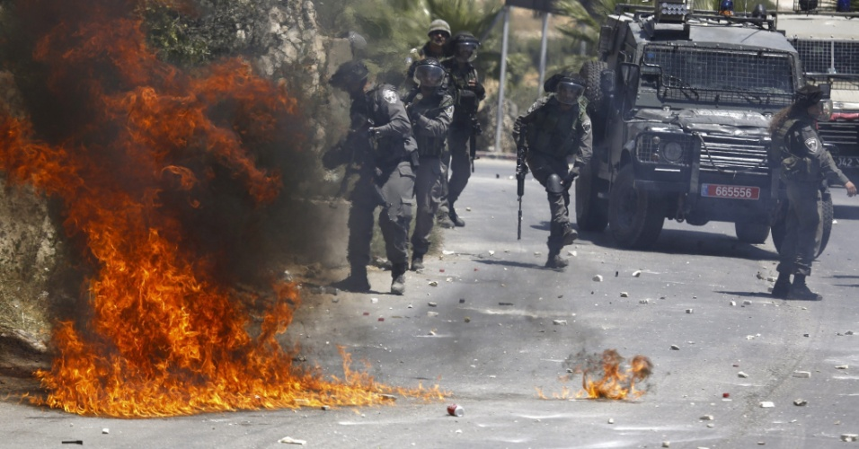 23.jul.2015 - Soldados israelenses enfrentam protesto de palestinos contra a morte de Falah Abu Maria, 53, em Beit Umar, Cisjordania. Segundo testemunhas, Abu Maria morreu após ser alvejado por forças de segurança israelenses durante uma patrulha noturna em uma aldeia de Beit Umar, al norte de Hebron. Um dos filhos do palestino ficou ferido durante a ação