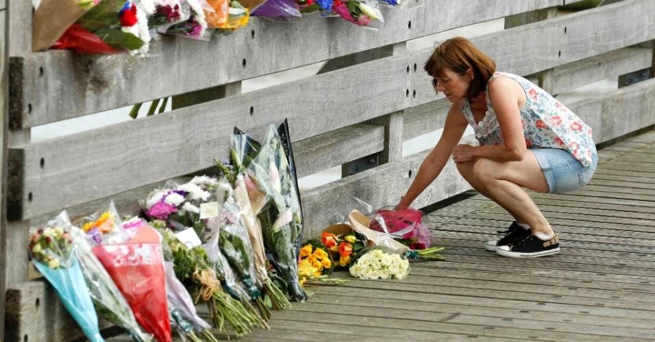 23.ago.2015 - Mulher coloca flores em homenagem a vítimas do acidente de avião que caiu em uma estrada durante exibição aérea em Shoreham, no Reino Unido. Neste domingo (23), a polícia elevou para 11 o número de mortos