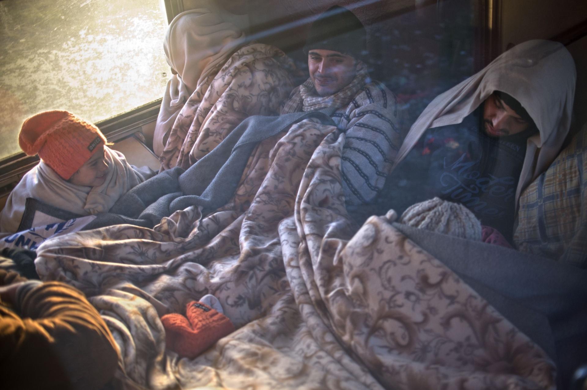 3.nov.2015 - Refugiados tentam se aquecer durante viagem de comboio entre Gevgelija, na fronteira greco-macedônia, para a Sérvia. Mais de 218 mil imigrantes e refugiados atravessaram o mediterrâneo rumo a Europa em outubro, mais do que todo o trânsito de refugiados feito no mesmo perímetro em 2014, segundo a ONU (Organização das Nações Unidas)