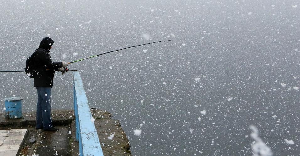 2.mai.2016 - Homem pesca em rio durante nevada na cidade de Divnogorsk, na região da Sibéria, na Rússia