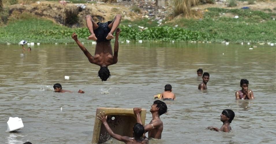 """22.mai.2016 - Crianças indianas brincam em um lago para aliviar o calor, em Nova Délhi, neste domingo. As temperaturas no país chegaram a 47 graus neste semana e o serviço meteorológico da Índia divulgou alertas sobre a """"severa onda de calor"""""""