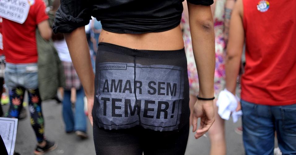 """29.mai.2016 - Participante da Parada Gay, em São Paulo, caminha com cartaz em protesto ao governo interino de Michel Temer, neste domingo. A parada deste ano foi marcado por gritos de """"Fora Temer"""" e manifestações contra o estupro coletivo de uma jovem no Rio de Janeiro"""