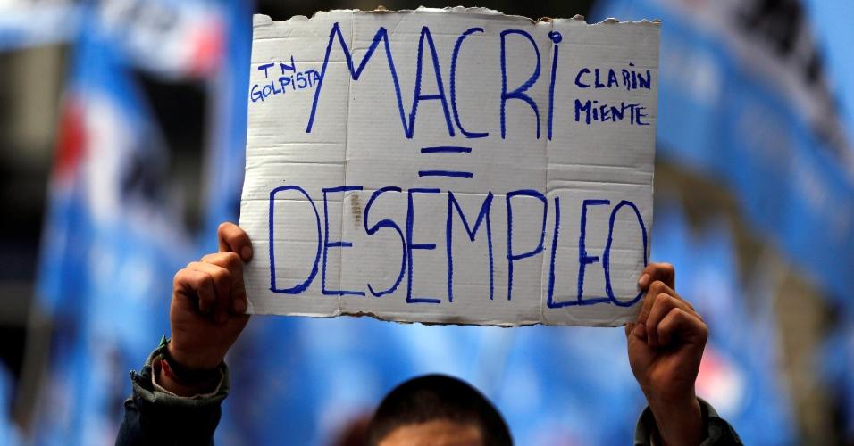 """2.jun.2016 - Manifestantes fazem protesto contra medidas econômicas do presidente Mauricio Macri em frente à Casa Rosada, sede do governo argentino, em Buenos Aires. Na foto, manifesta segura cartaz com a frase """"Macri igual desemprego"""". Em abril, o político foi citado pela investigação internacional """"Panama Papers"""" como diretor de duas empresas constituídas em paraísos fiscais. Na última segunda, ele afirmou que iria repatriar os 18 milhões de pesos (cerca de R$ 4,6 milhões) que mantém no paraíso fiscal das Bahamas"""