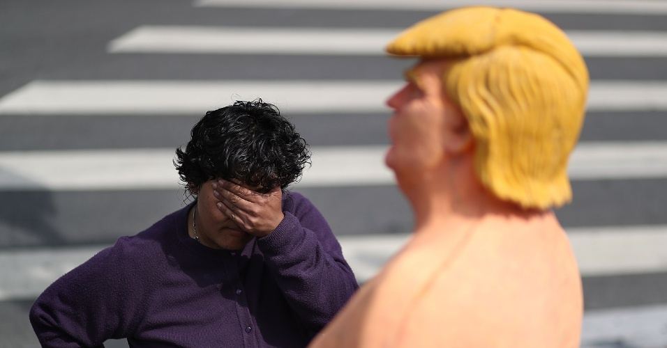 18.ago.2016 - Mulher cobre os olhos diante da estátua de Donald Trump, em San Francisco, EUA