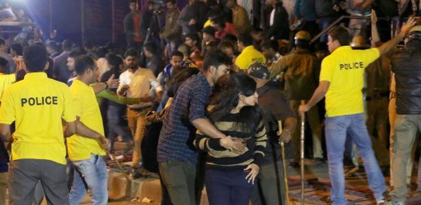 Indiano ajuda mulher enquanto policiais tentam controlar multidão durante comemoração do Ano-Novo em Bangalore