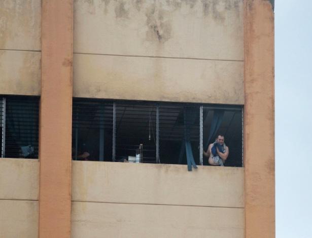 7.jul.2017 - Pessoa espera para ser retirada da prédio em chamas em San Salvador (El Salvador) - Jose Cabezas/Reuters