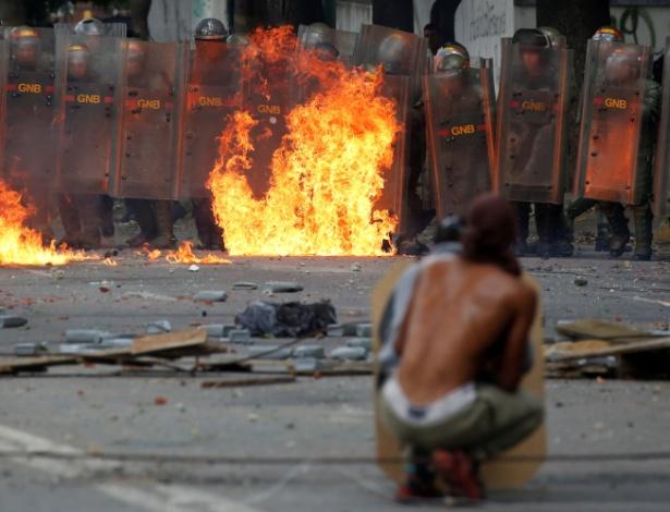 Manifestante e policiais durante confronto em protesto nesta quarta quarta em Caracas