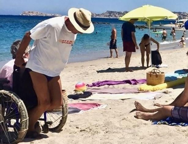 Homem carrega idosa em cadeira de rodas em cena que comoveu banhistas na Itália