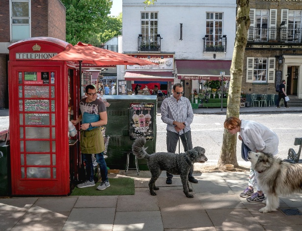 Homem trabalha em cabine telefônica transformada em um café em Londres