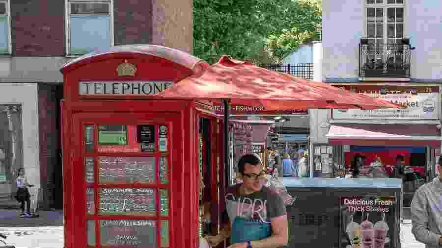 Homem serve café e bolos em uma cabine telefônica transformada em um café em Londres - Andrew Testa/The New York Times