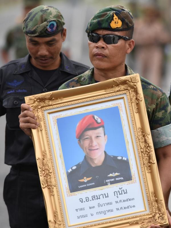 6.jul.2018 - Guarda de honra segura foto de Saman Kunan, 38, ex-integrante da unidade tailandesa de elite da marinha que morreu trabalhando para salvar 12 garotos e seu treinador presos na caverna