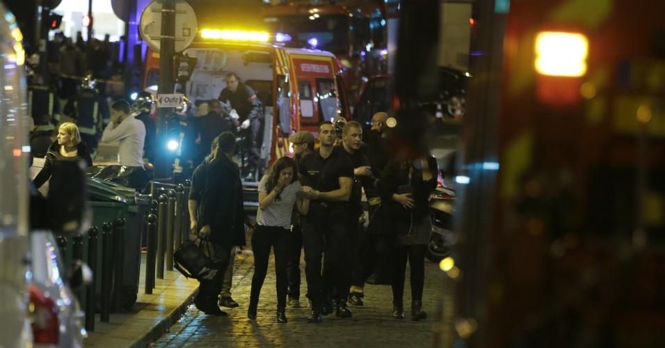 13.nov.2015 - Policiais franceses removem pessoas de rua em Paris, na França, após uma série de ataques na capital francesa. Tiroteios e explosões aconteceram na noite desta sexta-feira (13) na capital francesa. A polícia relatou ao menos duas explosões nas proximidades do estádio Stade de France, onde o presidente francês, François Hollande, acompanhava um amistoso da seleção francesa