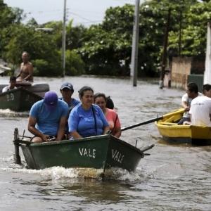 Pessoas usam barco para transitar em rua alagada de Assunção, no Paraguai, em dezembro