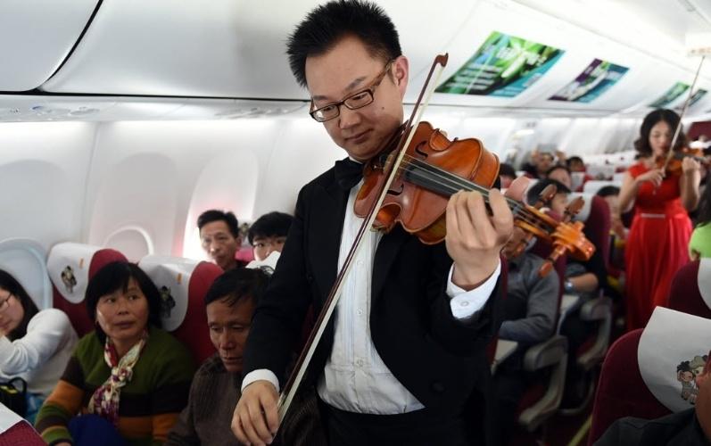 31.jan.2016 - Músicos tocam violino para os passageiros de voo na China neste domingo (31) para comemorar a chegada do Ano Novo chinês