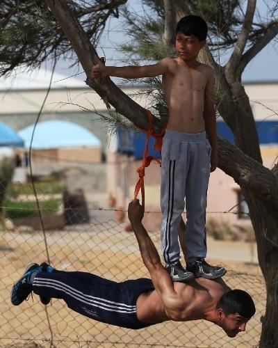 3.jun.2016 - O menino Ahmed Faseh se equilibra sobre as costas de Mahmud Nasman, durante acrobacia em árvore na cidade de Gaza, na Palestina. Os dois integram o grupo Bar Palestine de esporte de rua. A prática, nova na faixa de Gaza, tem se propagado por diversas cidades do mundo