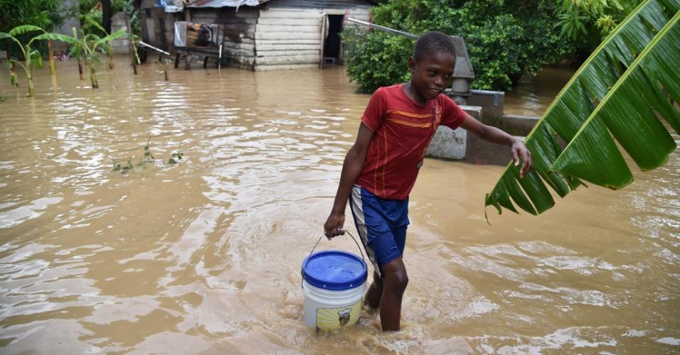 5.out.2016 - Garoto leva balde de água limpa para casa, na comuna de Leogane, em Porto Príncipe, Haiti, na manhã seguinte à passagem do furacão Matthew
