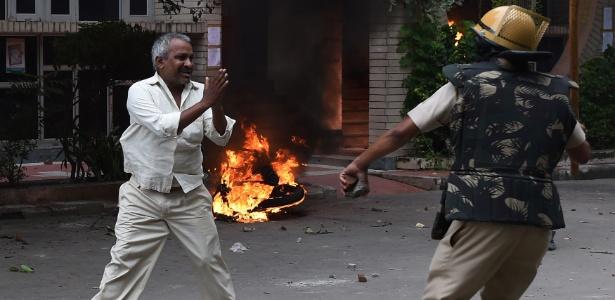 25.ago.2017 - Seguidor do líder espiritual Gurmeet Ram Rahim Singh pede não agressão a policial após ser acertado com um bastão durante os protestos pela condenação do guru por dois estupros - AFP PHOTO / MONEY SHARMA