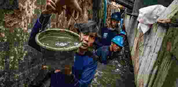 8.nov.2017 - Homens trabalham em um muro que desabou em casas inundadas em uma favela em Jacarta,na Indonésia - Josh Haner/The New York Times - Josh Haner/The New York Times
