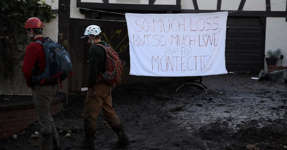 10.jan.2018 - Pessoas caminham em frente de casa onde foi colocada uma faixa pedindo orações para Montecito