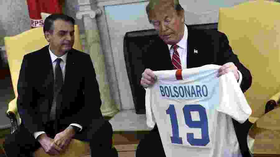 19.mar.2019 - Presidente dos EUA Donald Trump troca camisas de futebol com o presidente Jair Bolsonaro - Brendan Smialowski/AFP