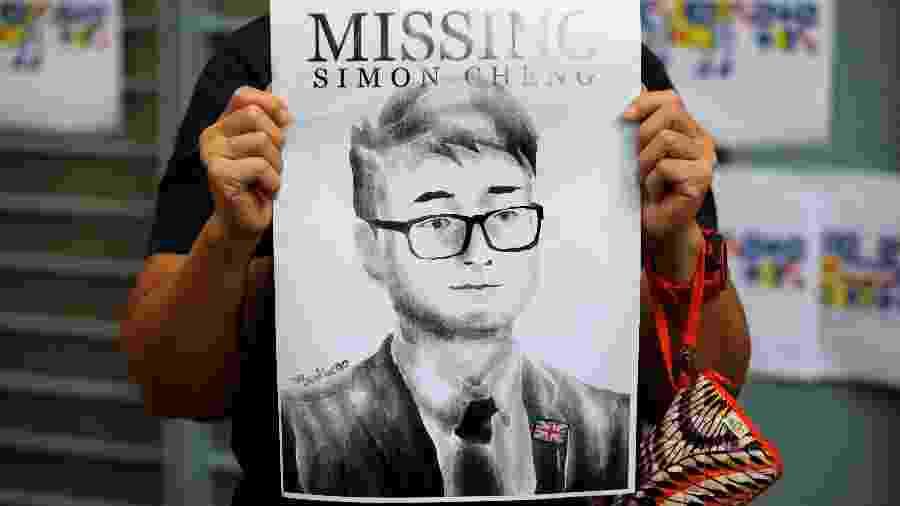 Uma mulher segura o cartaz de desaparecido do funcionário do consulado britânico Simon Cheng - Willy Kurniawan/Reuters