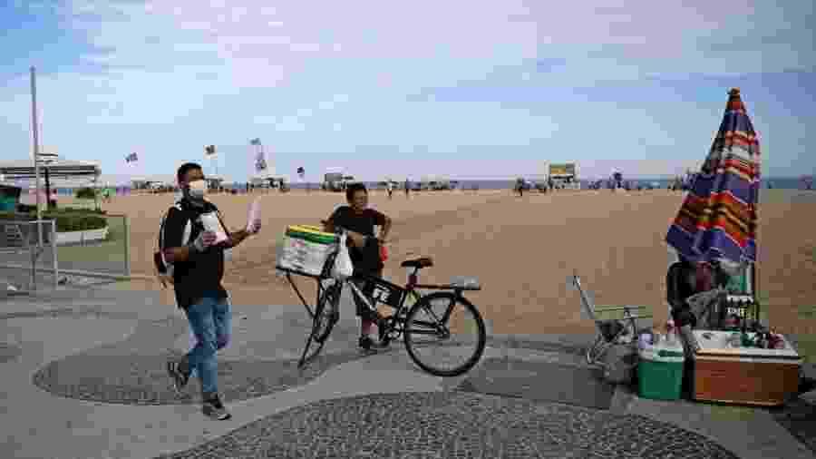 20.03.2020 - Vendedor ambulante usa máscara de proteção durante tarde na praia de Copacabana, no Rio de Janeiro, esvaziada em função do temor de coronavírus - Carl de Souza/AFP