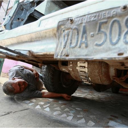 Alfredo Gonzales verifica um reservatório de gás de cozinha embaixo do carro, em Maracaibo (Venezuela) - Isaac Urrutia/Reuters