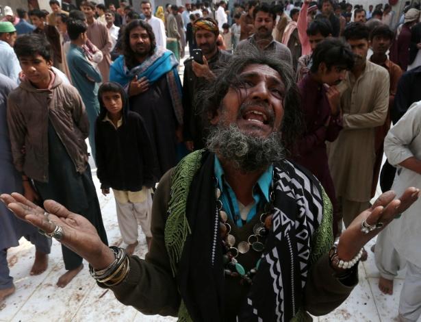 Homem lamenta ataque suicida em templo sufista em Sehwan Sharif, no Paquistão
