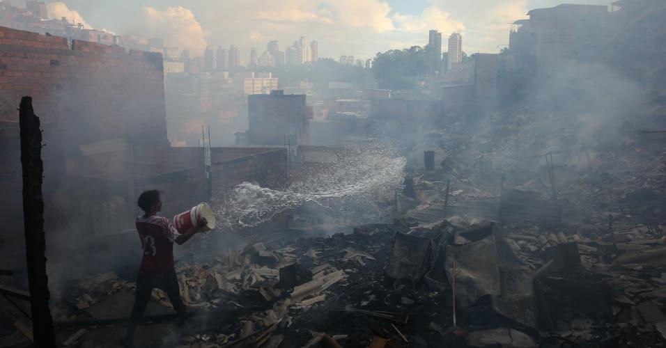 1.mar.2017 - Morador ajuda a apagar um incêndio de grandes proporções que atingiu cerca de 50 barracos na favela de Paraisópolis, na zona sul de São Paulo
