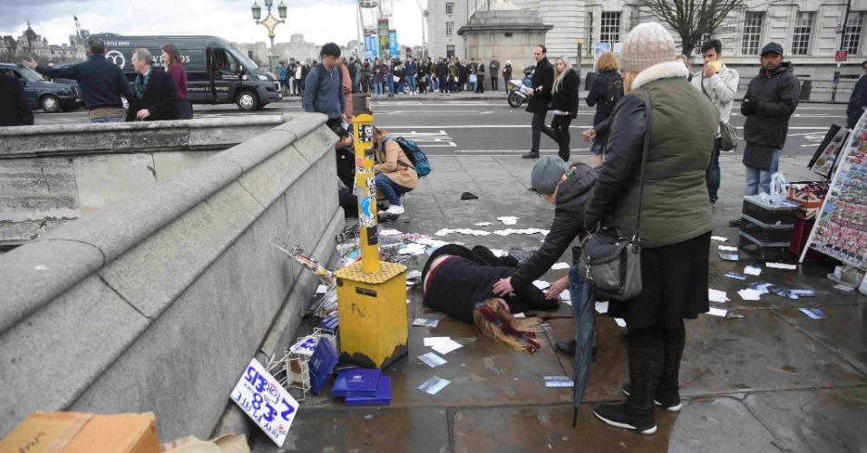 22.mar.2017 - Mulheres tentam ajudar ferida em tiroteio na Westminster Bridge, próximo ao Parlamento britânico, em Londres