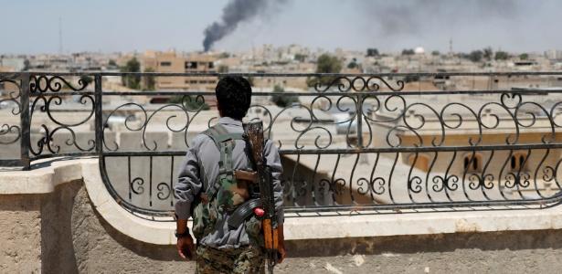 Soldado da Unidade de Proteção das Pessoas observa fumaça na cidade de Raqqa na Síria - GORAN TOMASEVIC/REUTERS