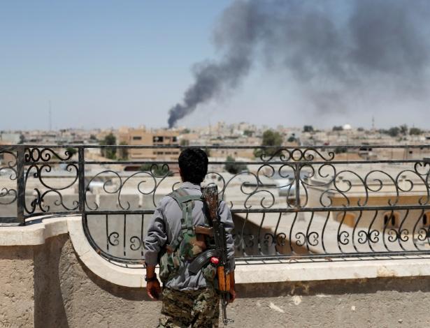 Soldado da Unidade de Proteção das Pessoas observa fumaça na cidade de Raqqa na Síria