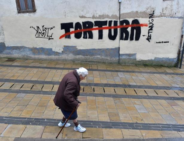 Idosa passa em frente à pichação contra a tortura em Agurain, no País Basco