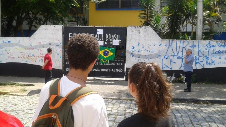 Luiz e Carla olham para a escola a partir da calçada na frente da casa da aluna - Nathan Lopes/UOL