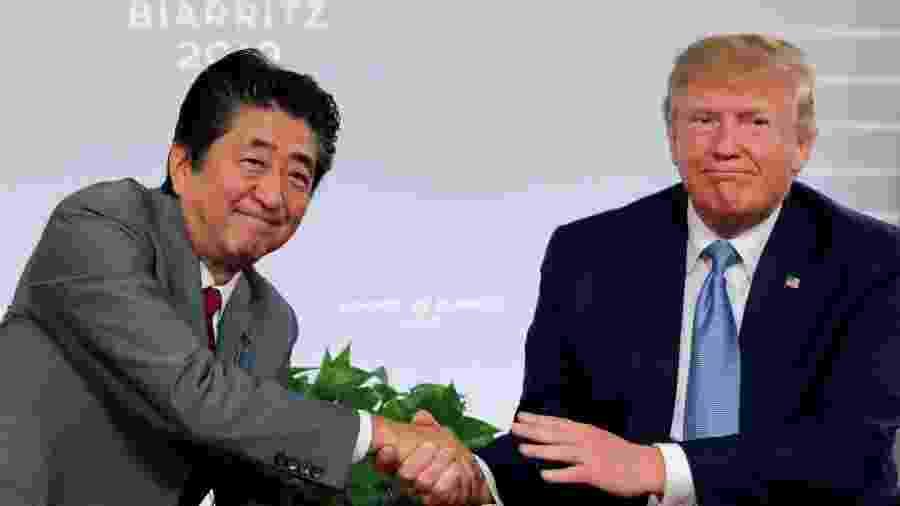 25.ago.2019 - O primeiro-ministro do Japão, Shinzo Abe, cumprimente o presidente dos EUA, Donald Trump, durante reunião do G7 - Carlos Barria/Reuters