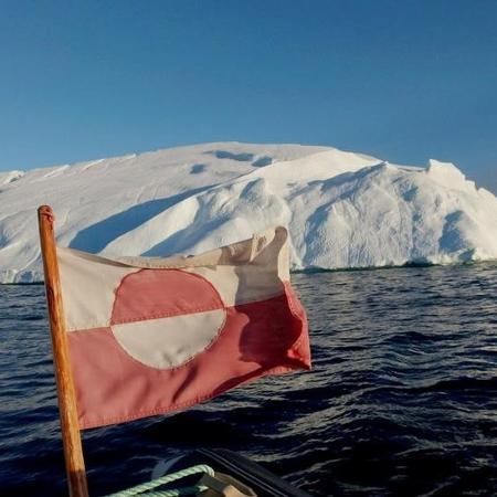 Bandeira da Groenlândia nos arredores de iceberg perto de Ilulissat -