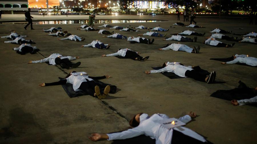 Enfermeiros deitam no chão em protesto, no ano passado, lembrando profissionais de saúde que morreram - ADRIANO MACHADO/REUTERS