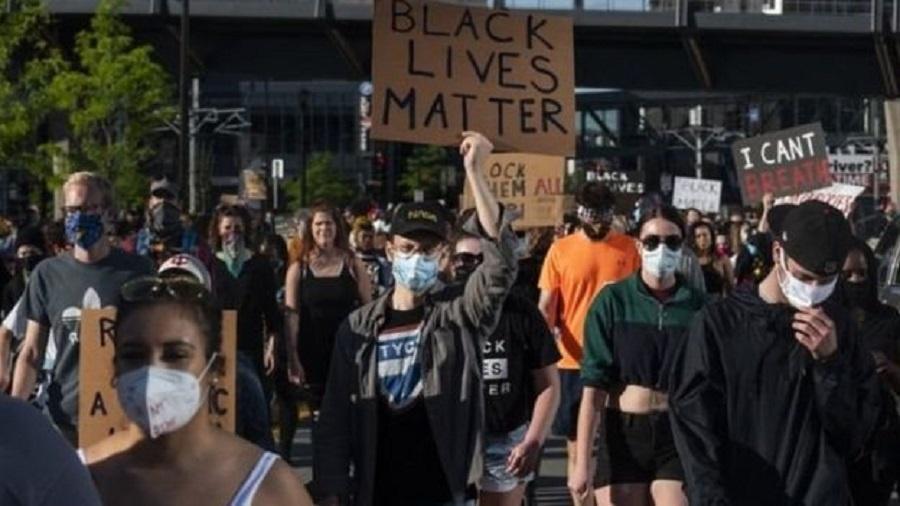 Manifestantes posam do lado de fora de loja de bebidas em chamas nos Estados Unidos - Reuters via BBC