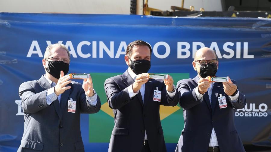 O governador de São Paulo, João Doria (PSDB), o secretário estadual de Saúde, Jean Gorinchteyn, e o diretor do Instituto Butantan, Dimas Covas, recebem doses da CoronaVac no Aeroporto Internacional de Guarulhos, em São Paulo - Governo de São Paulo/Divulgação