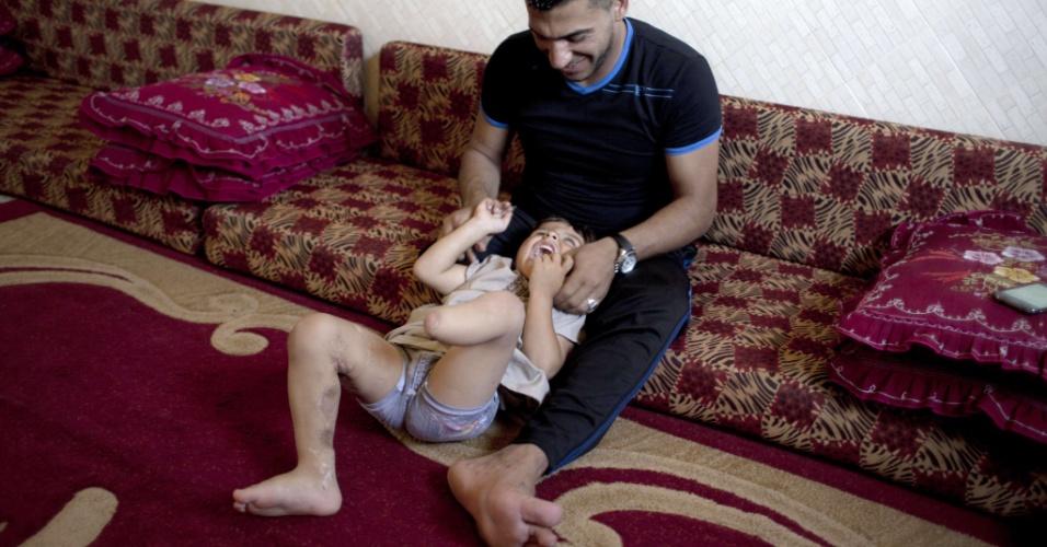 29.jul.2015 - Wael al-Namla, 26, brinca com o filho Sharif na sala de estar de sua casa em Rafah, no sul da faixa de Gaza. Wael al-Namla teve um dos membros amputados durante a guerra de 50 dias entre Israel e militantes do Hamas no verão de 2014 (no hemisfério Norte), durante um ataque israelense que ficou conhecido como
