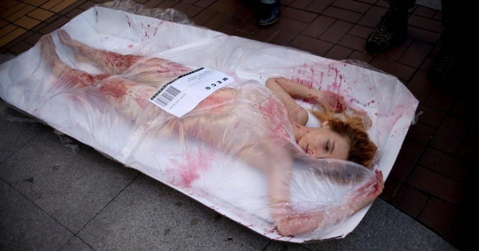 """8.mai.2016 - Ativista deitada em imitação gigante de embalagem de carne faz protesto em defesa dos direitos dos animais em Sofia, na Bulgária. Na embalagem, lê-se o lema da campanha """"Carne é assassinato"""""""
