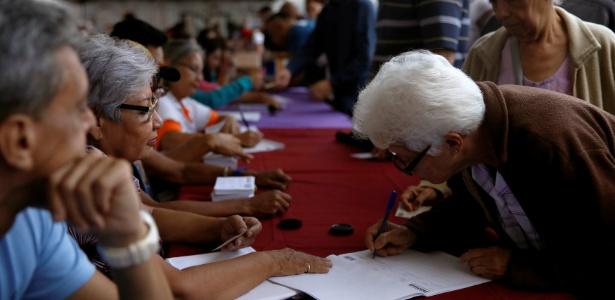 Mulher deixa sua assinatura durante um plebiscito não oficial contra o presidente venezuelano Nicolás Maduro sobre sua tentativa de reformular a Constituição, em Caracas, na Venezuela