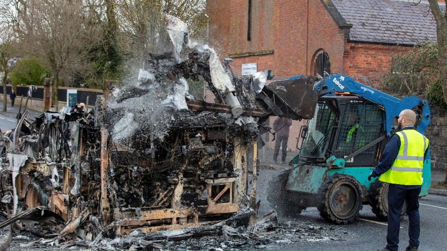 Funcionários limpam restos de ônibus queimado em Belfast, Irlanda do Norte, depois de o veículo ter sido incendiado em noite de violência - Paul Faith/AFP
