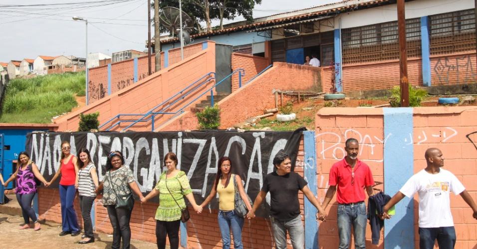 13.nov.2015 - Professores fizeram um abraço simbólico em frente a Escola Estadual Presidente Salvador Allende Gossens, no bairro José Bonifácio, na zona leste de São Paulo. A escola foi ocupada por estudantes na quinta-feira. Professores e alunos são contra o fechamento da unidade