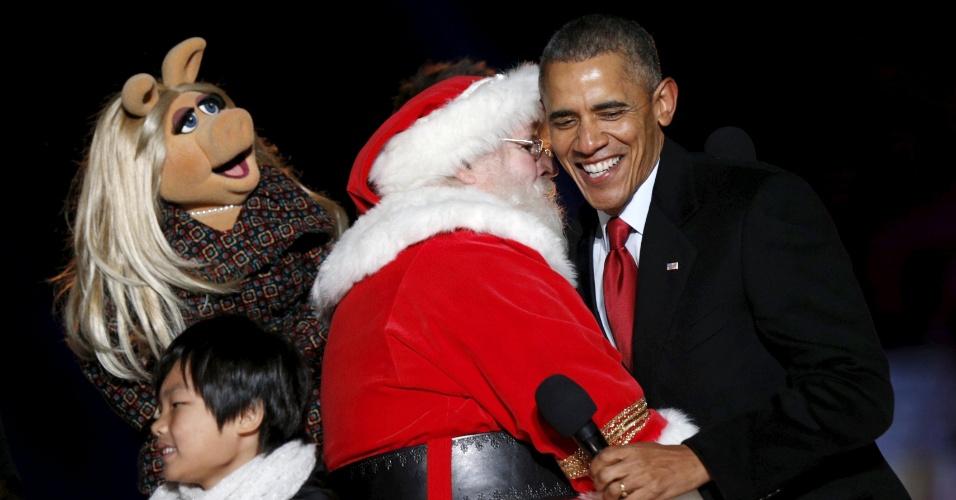 4.dez.2015 - O presidente dos Estados Unidos, Barack Obama, é abraçado por um Papai Noel e pela Piggy, dos Muppets, durante a tradicional cerimônia de inauguração da iluminação da árvore de Natal da Casa Branca, em Washington D.C. A cerimônia, que acontece todos os anos, foi realizada pela 93ª vez