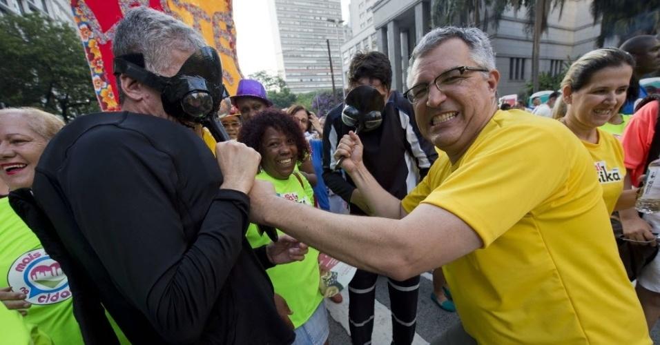 """4.fev.2016 - O secretário de Saúde de São Paulo, Alexandre Padilha (PT-SP), """"briga"""" com dois homens fantasiados de Aedes aegypti durante bloco de carnaval na cidade de São Paulo"""