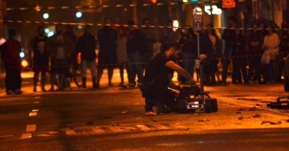 22.jul.2016 - Agente do Esquadrão Antibombas da Polícia Civil examina uma bolsa abandonada na noite desta quinta-feira (21) na rua Voluntários da Pátria, em Botafogo, na zona sul do Rio de Janeiro. A via, na altura do número 381 da rua Camuirano, foi fechada. Após análise da bolsa, a polícia informou que não era uma bomba